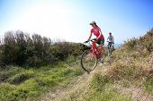 picture of bike path  - Couple riding bike on country path - JPG