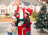 Happy children embracing Santa Claus in courtyard