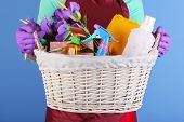 pic of spring-cleaning  - Housewife holding basket with cleaning equipment on color background - JPG