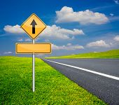 picture of traffic sign  - straight traffic sign with blank signs beside asphalt road and blue sky with green meadow - JPG