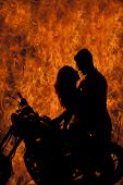 Постер, плакат: Silhouette Couple Kiss On Motorcycle Fire