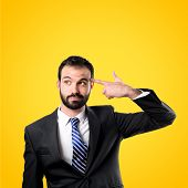foto of suicide  - Young businessman committing suicide over yellow background - JPG