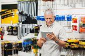 stock photo of hardware  - Smiling senior customer holding digital tablet in hardware shop - JPG