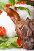 picture of roast duck  - Roasted duck leg on a background of rice and vegetables macro vertical - JPG