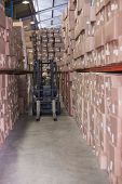 stock photo of forklift driver  - Forklift driver operating the machine in a large warehouse - JPG