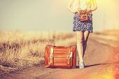 picture of country girl  - girl with suitcase and camera on country road - JPG