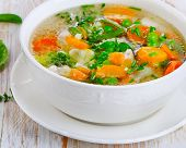 picture of vegetable soup  - Soup with chicken and vegetables on a wooden table  - JPG