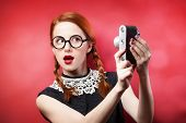 stock photo of redhead  - Redhead girl with retro camera on red background - JPG