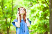 picture of redhead  - Redhead women with headphones in the park - JPG