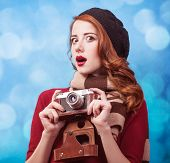 stock photo of beret  - Redhead women in beret with camera on blue background - JPG