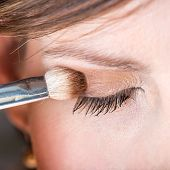 image of  eyes  - Fashion and beauty concept of a woman applying eye shadow to her eyelid with an applicator closeup detail of one eye - JPG