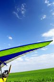 pic of glider  - Motorized hang glider over green grass ready to fly - JPG
