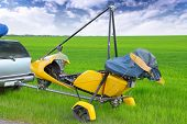 foto of glider  - Motorized hang glider over green grass ready to fly - JPG