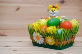 stock photo of easter eggs bunny  - easter bunny with easter eggs in a basket on the wooden background - JPG