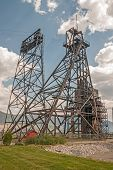 image of open-pit mine  - The historic Belmont Mine headframe with the Montana Resources open pit mine in the background - JPG
