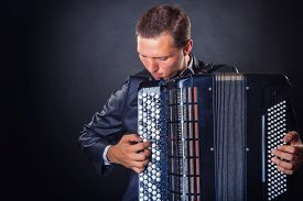 pic of accordion  - Young man with accordion on a black background with copy space - JPG