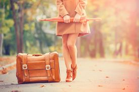 stock photo of grils  - Gril in coat with umbrella and suitcase in the park - JPG