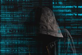stock photo of hoods  - Faceless hooded anonymous computer hacker with programming code from monitor - JPG