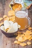 stock photo of potato chips  - Beer with foam in glass mug and potato chips in bowl on wooden table - JPG