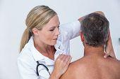 picture of shoulders  - Doctor examining her patient shoulder in medical office - JPG