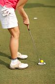 stock photo of ladies golf  - Cropped imager of lady golfer hitting ball in a hole - JPG