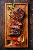pic of ribeye steak  - Sliced medium rare grilled Beef steak Ribeye with grilled onions and cherry tomatoes on cutting board on wooden background - JPG
