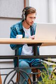 stock photo of concentration man  - Concentrated young man in headphones working on laptop while sitting at sidewalk cafe - JPG
