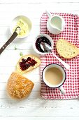 image of milkman  - fresh bread toast with jam and butter and tea with milk on a light wooden surface - JPG