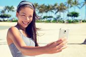pic of multicultural  - Selfie taking young fitness happy woman on palm beach with smartphone after workout - JPG