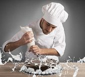 image of pastry chef  - Pastry chef decorates a cake with cream - JPG