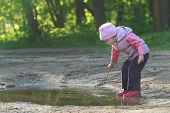 picture of naturalist  - Toddler preschooler is exploring summer puddle wearing red gums thin tree twig in hand