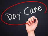 picture of day care center  - Man Hand writing Day Care with marker on transparent wipe board - JPG