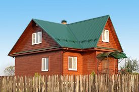 foto of louvers  - Wooden house under green metal roof with white plastic windows with jalousie photo - JPG