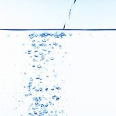 stock photo of drinking water  - stock photo of water bubbles pouring water into clear water - JPG