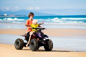 Teenager And His Little Brother Riding Quad Bike On Tropical Beach. Active Teen Age Boy On Quadricyc poster