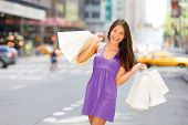 Shopper woman holding shopping bag walking in New York City having fun outside in NYC summer. Asian  poster