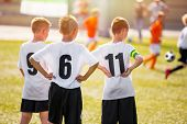 Kids Soccer Team Players Standing On Grass Pitch On A Sunny Day. Young Boys Watching Soccer Match. Y poster