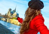 Bright In Paris. Modern Woman In Red Trench Coat On Embankment Near Notre Dame De Paris In Paris, Fr poster