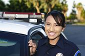image of lightbar  - a smiling Hispanic police officer standing next to her patrol car - JPG