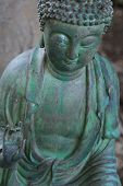 stock photo of siddhartha  - An patina and distressed statue of Buddha - JPG