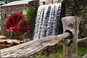 picture of split rail fence  - View of a split rail fence with a grist mill and waterfall in the background - JPG