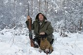 foto of jagdterrier  - A hunter with a dog in winter forest - JPG