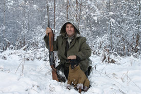 picture of jagdterrier  - A hunter with a dog in winter forest - JPG
