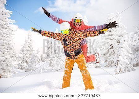 poster of Happy Couple Skier And Snowboarder Are Having Fun At Ski Resort. Ski Winter Sports Concept
