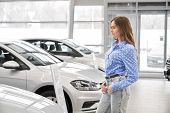 Side View Of Young Female Client Standing In Auto Salon And Choosing New Car. Pretty Woman Looking A poster