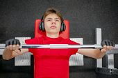 Cute Young Man In Sportswear And Headphones Doing Barbell Press In The Gym, Teen Engaged In The Gym, poster