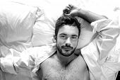 Overhead Portrait Of Sexy, Hairy Muscular Man With Open Shirt Lying In Bed On Pillows And Looking Up poster
