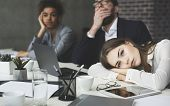 Boring Presentation. Young Business People Looking Bored, Woman Lying On Table And Looking Away poster