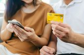 Young Couple Using Mobile Smart Phone For Paying Credit Card And Family Budget Expense Cost Bills Si poster