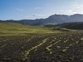 Volcanic Landscape With Snow Covered Mountains, Green Hills And Lava Gravel Ground Covered By Lush M poster